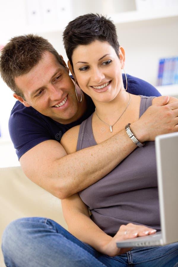 Pares del amor usando el ordenador portátil fotos de archivo