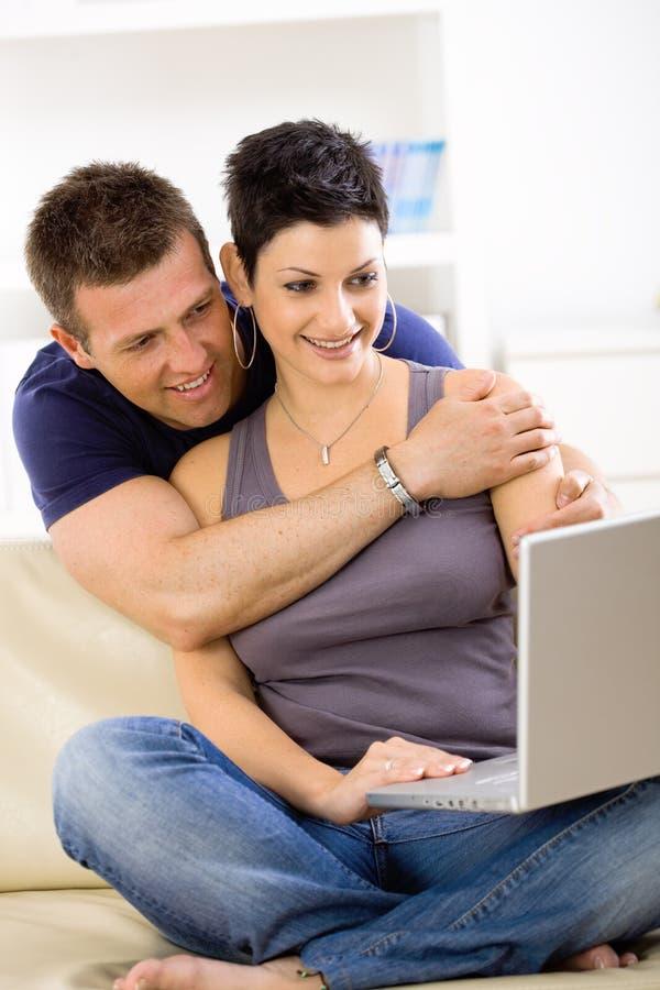 Pares del amor usando el ordenador portátil fotografía de archivo libre de regalías