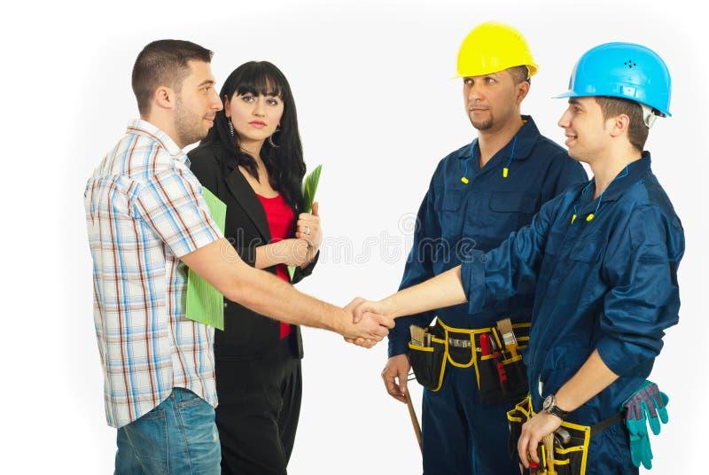 Pares del apretón de manos con los trabajadores del constructor fotos de archivo libres de regalías