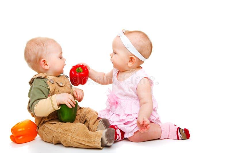 Pares del bebé que comen las pimientas imágenes de archivo libres de regalías