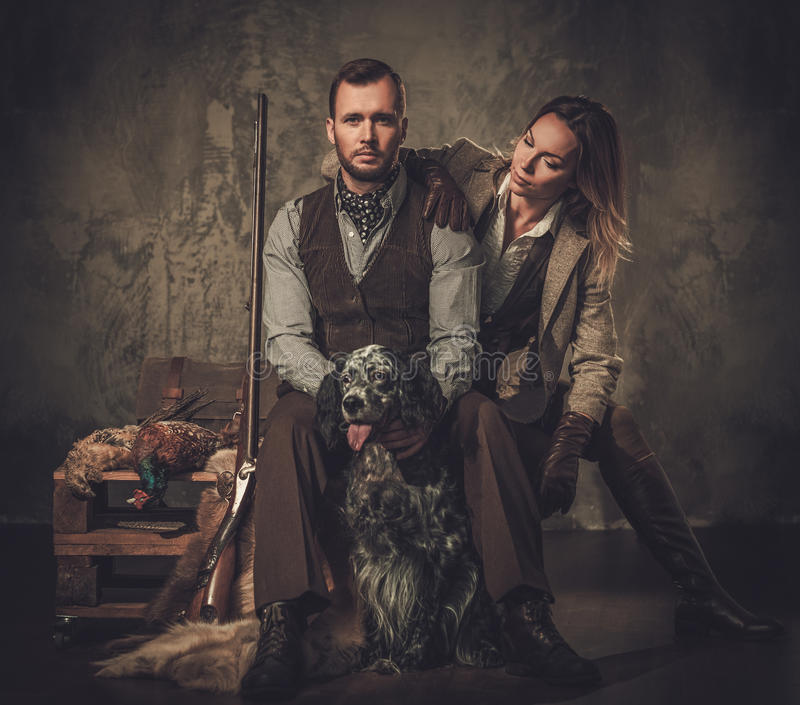 Pares del cazador con un organismo inglés y una escopeta en una ropa tradicional del tiroteo, sentada en un fondo oscuro foto de archivo