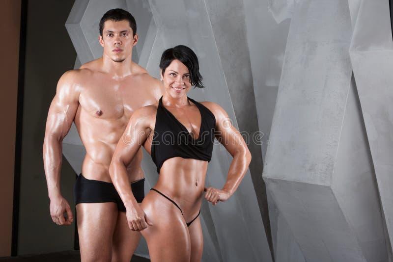 Pares del culturista bien entrenado con pesas de gimnasia imágenes de archivo libres de regalías