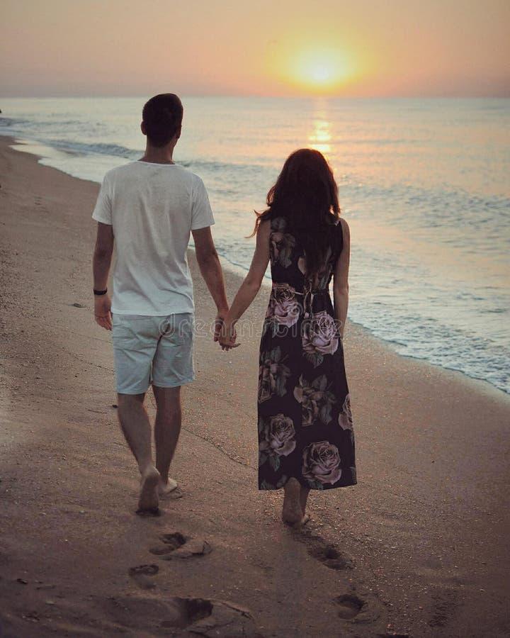 Pares del hombre joven y de la mujer que caminan en la costa de la playa cerca del mar y que miran en la salida del sol fotos de archivo libres de regalías