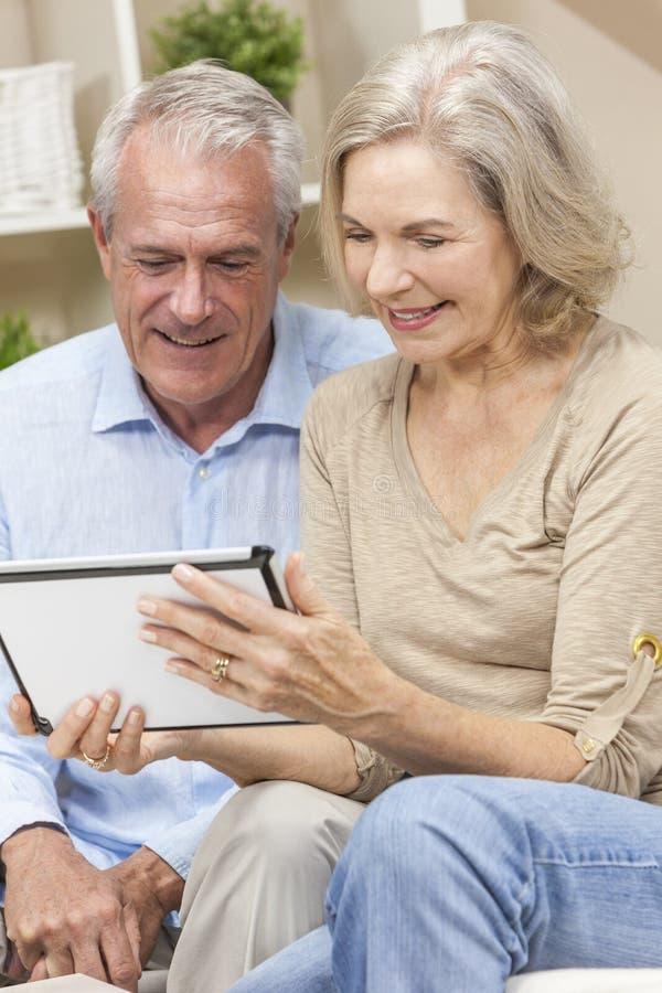Pares del hombre mayor y de la mujer en el ordenador de la tablilla fotos de archivo libres de regalías
