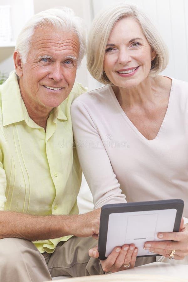 Pares del hombre mayor y de la mujer usando el ordenador de la tablilla fotos de archivo libres de regalías
