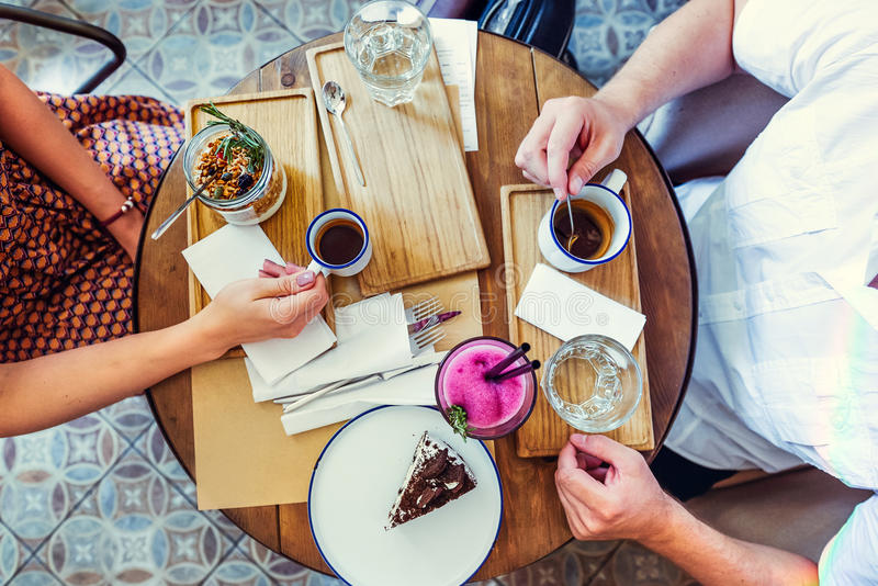 Pares del hombre y de la mujer el la fecha que desayuna en la mañana en café Granola, torta de chocolate, smoothie y café calient fotografía de archivo libre de regalías