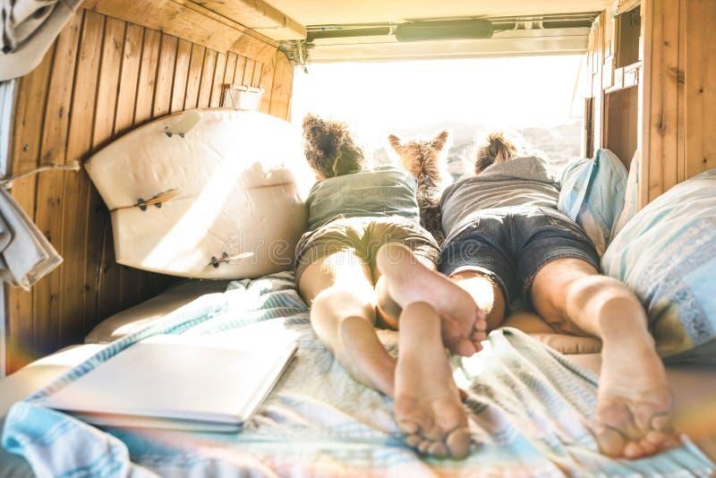 Pares del inconformista con el perro lindo que viaja junto en la mini furgoneta del vintage imágenes de archivo libres de regalías