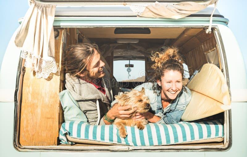 Pares del inconformista con el perro lindo que viaja junto en la mini furgoneta del vintage fotos de archivo libres de regalías