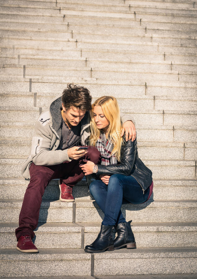 Pares del inconformista en el amor que se divierte con smartphone imagen de archivo