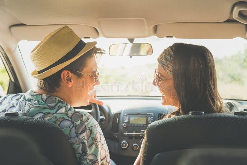 Pares del inconformista que se sientan en coche y que disfrutan de viaje por carretera fotos de archivo libres de regalías