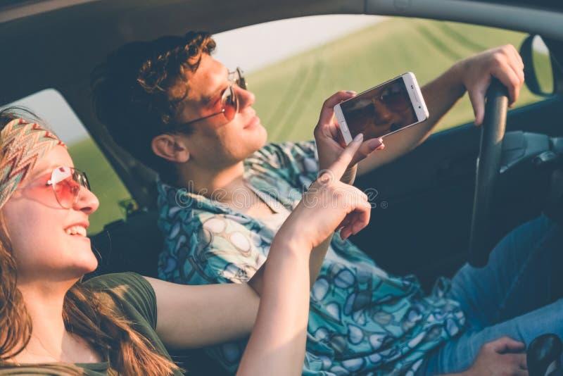 Pares del inconformista que se sientan en coche y que usan el teléfono elegante de la pantalla táctil imagen de archivo libre de regalías