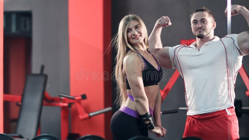 Pares del levantamiento de pesas que plantean la mirada en el espejo del gimnasio foto de archivo