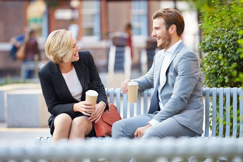 Pares del negocio en banco de parque con café imagenes de archivo
