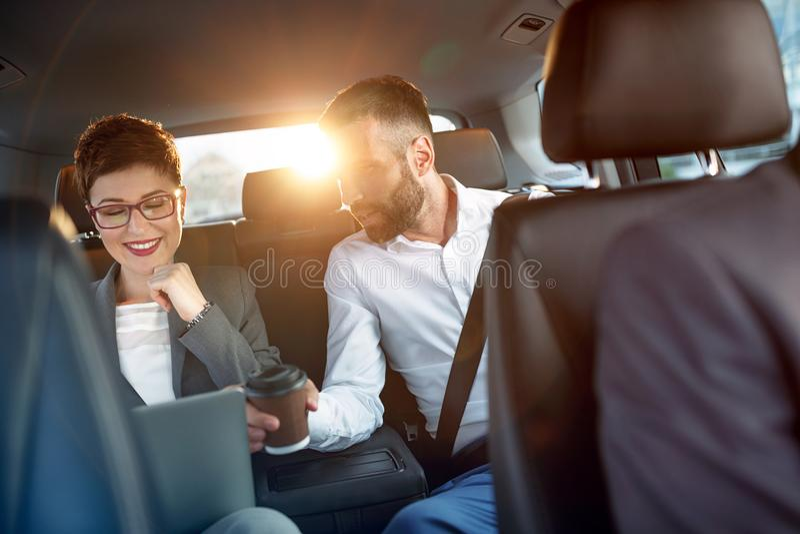 Pares del negocio en el coche en viaje de negocios foto de archivo libre de regalías