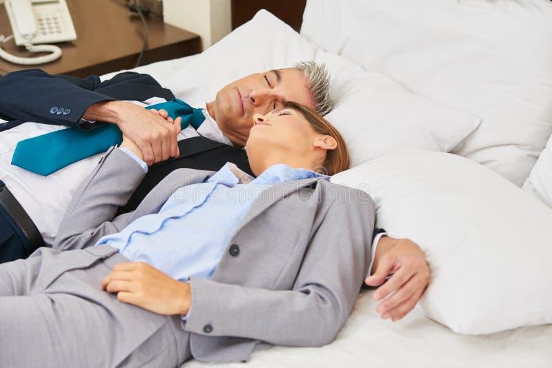 Pares del negocio que duermen en cama en hotel imagen de archivo