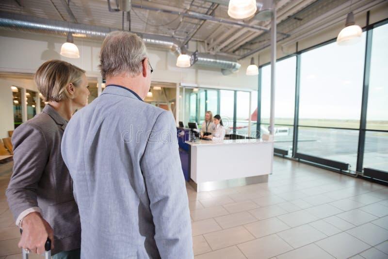 Pares del negocio que miran a los recepcionistas que trabajan en aeropuerto fotografía de archivo