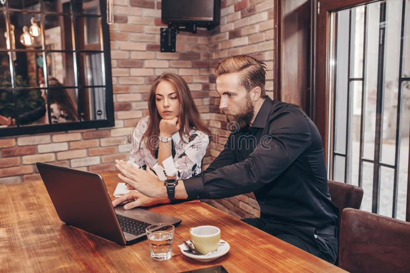 Pares del negocio usando el ordenador portátil y tener una conversación fotos de archivo