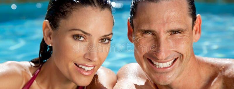 Pares del panorama que se relajan en piscina con sonrisas perfectas de los dientes imagenes de archivo