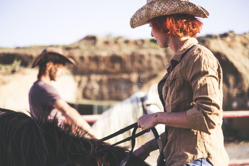 Pares del paseo moderno del vaquero junto un hombre y una mujer con dos caballos imagen caliente del filtro para la forma de vida imagen de archivo libre de regalías