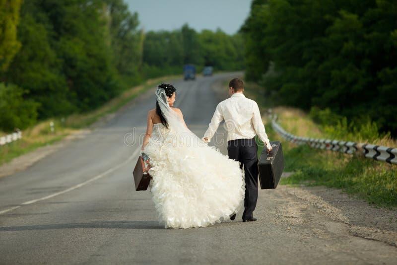 Pares del recién casado con las maletas de efectivo imagen de archivo libre de regalías
