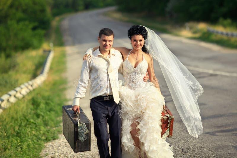 Pares del recién casado con las maletas de efectivo foto de archivo libre de regalías