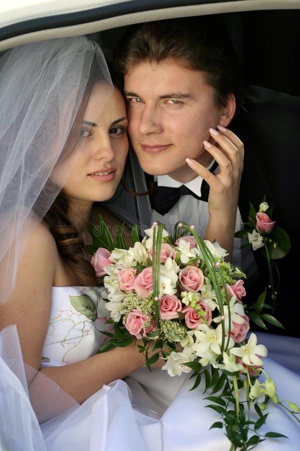 Pares del recién casado en limo del coche de la boda imágenes de archivo libres de regalías