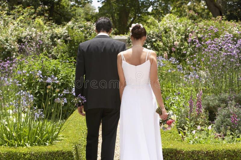 Pares del recién casado que caminan en jardín fotos de archivo