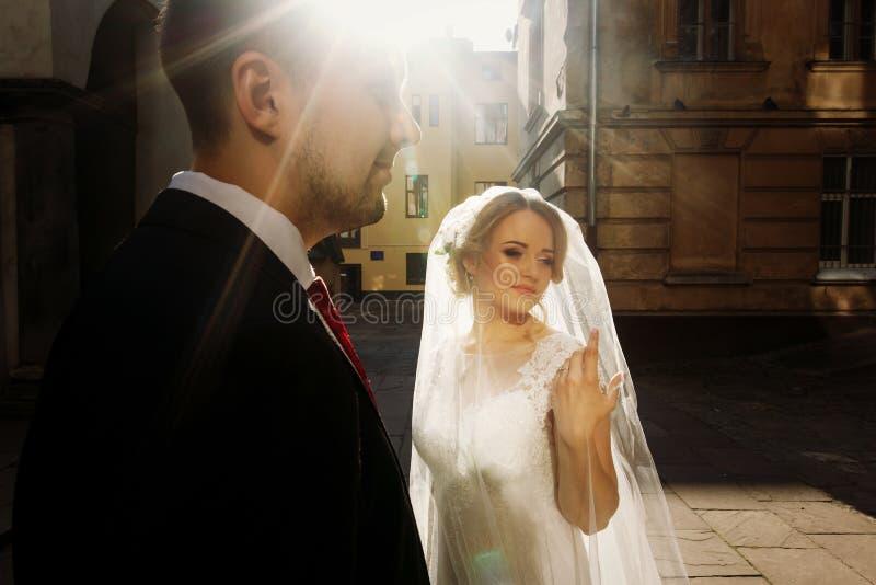 Pares del recién casado que se colocan en la calle, novia rubia hermosa en wh imagenes de archivo