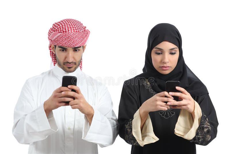 Pares del saudí enviciados al teléfono elegante fotografía de archivo libre de regalías