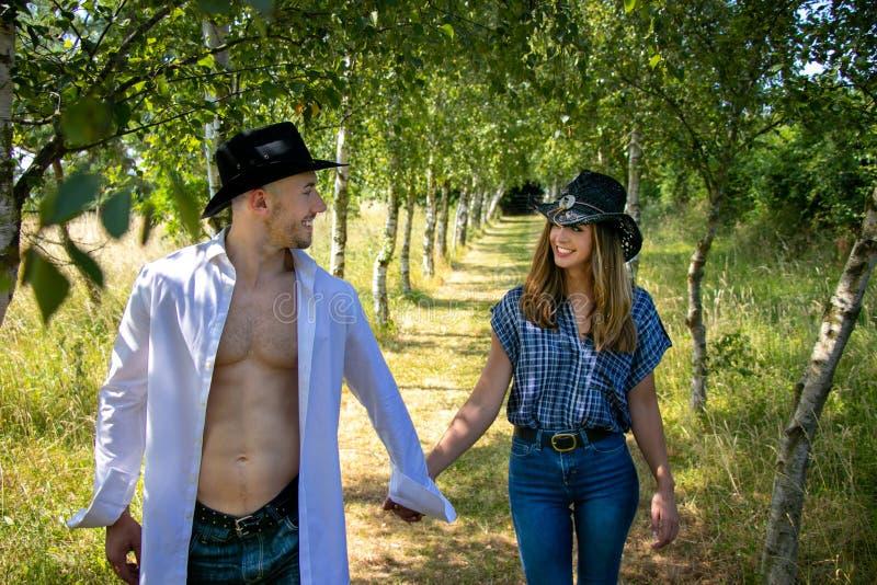 Pares del vaquero y de la vaquera con las manos del control de los sombreros como caminan a través de la avenida de árboles en ra imagen de archivo libre de regalías