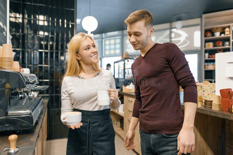 Pares del varón joven y de los dueños de cafetería femeninos cerca del contador, hablando y sonriendo, concepto del negocio de la foto de archivo
