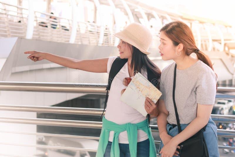 Pares del viajero con las mochilas usando mapa local genérico y el señalar al lado derecho el día soleado fotografía de archivo