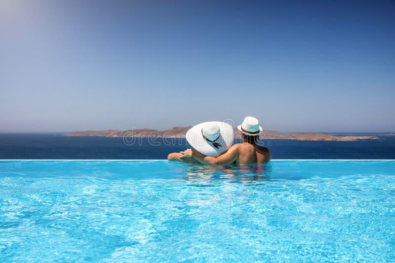 Pares del viajero en una piscina del infinito que goza del mar Mediterráneo fotografía de archivo