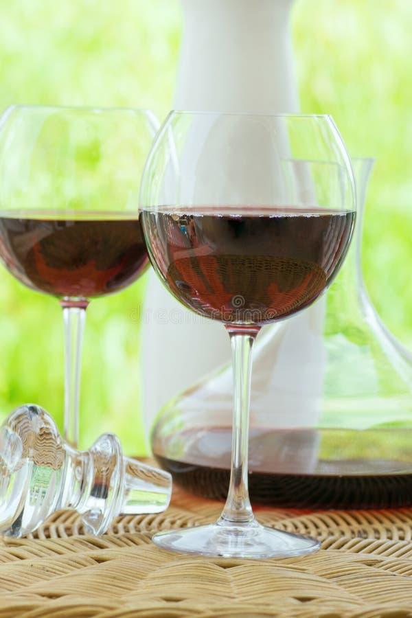 Pares del vidrio con el vino rojo y la jarra en la tabla de mimbre de la rota en la terraza del jardín del chalet o de la mansión imagenes de archivo