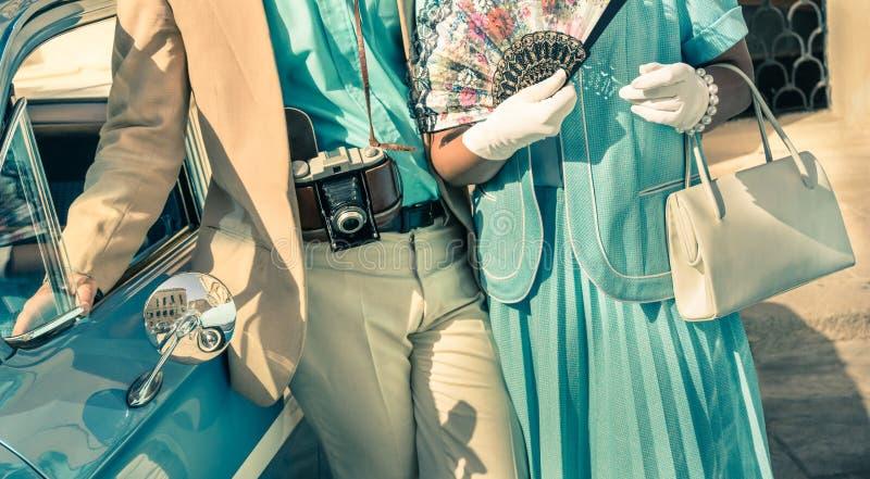 Pares del vintage que presentan con el coche clásico siguiente de la ropa retra fotografía de archivo libre de regalías