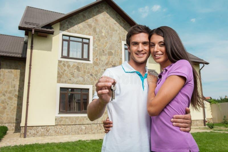 Pares delante del nuevo hogar que lleva a cabo llaves de la puerta fotos de archivo