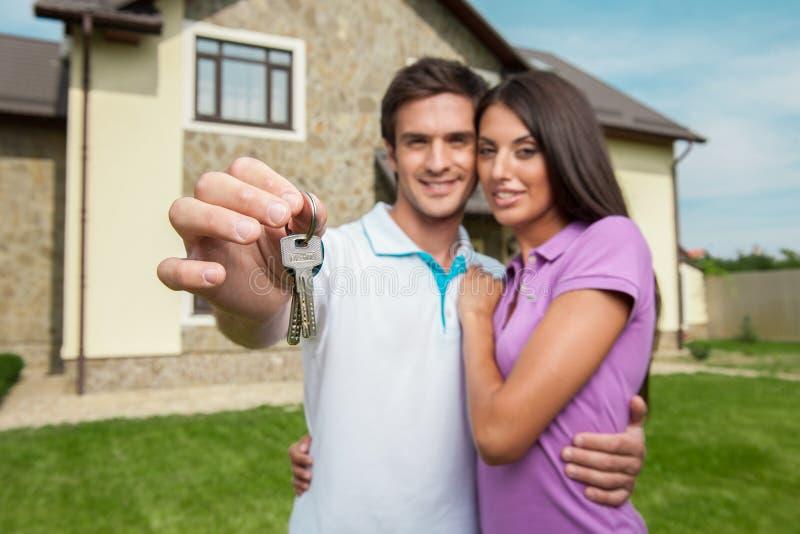Pares delante del nuevo hogar que lleva a cabo llaves de la puerta imagen de archivo libre de regalías