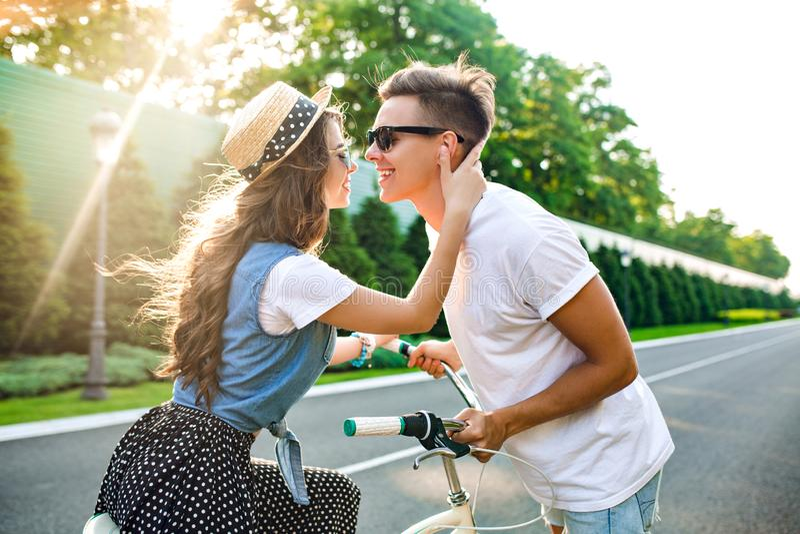 Pares delicados no amor na estrada no por do sol A menina bonita com cabelo encaracolado longo senta-se na bicicleta, indivíduo c fotos de stock