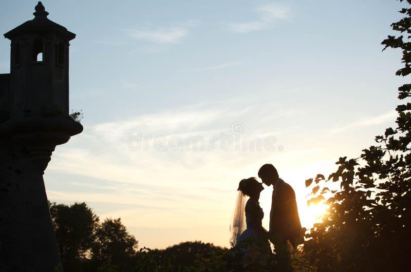 Pares delicados que guardam as mãos e que beijam no castelo do fundo fotografia de stock