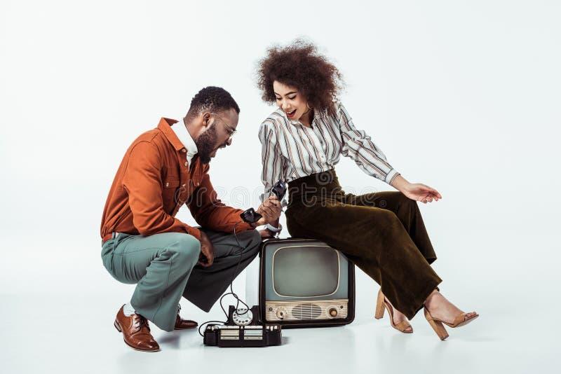 pares denominados retros afro-americanos que olham com surpresa no telefone do vintage foto de stock