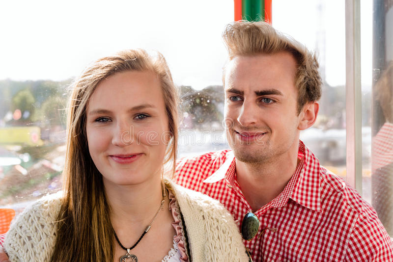 Pares dentro de uma roda de Ferris em Oktoberfest imagens de stock royalty free