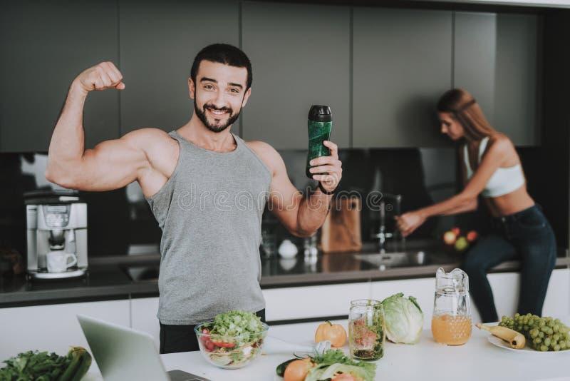 Pares deportivos en concepto de la cocina Demostración del bíceps imagenes de archivo