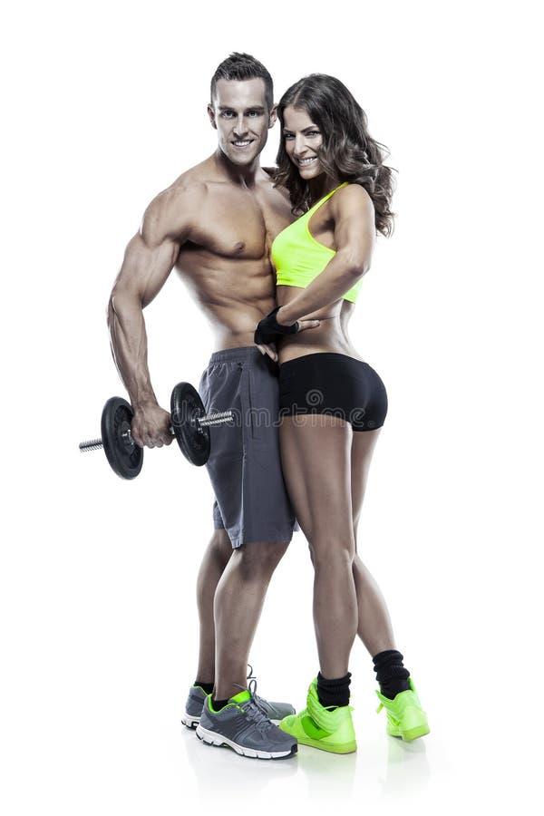 Pares deportivos jovenes de la aptitud hermosa con pesa de gimnasia foto de archivo libre de regalías
