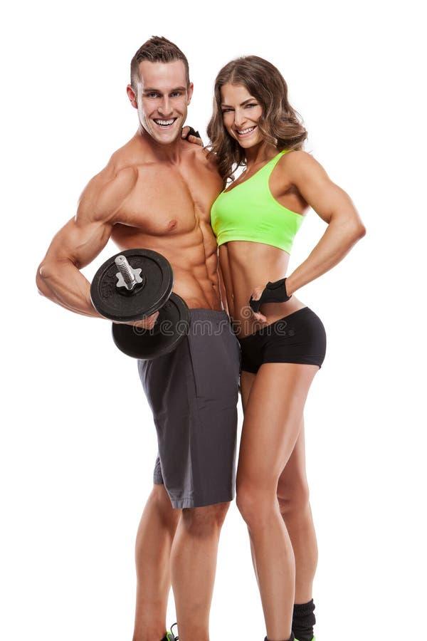 Pares deportivos jovenes de la aptitud hermosa con pesa de gimnasia imagen de archivo