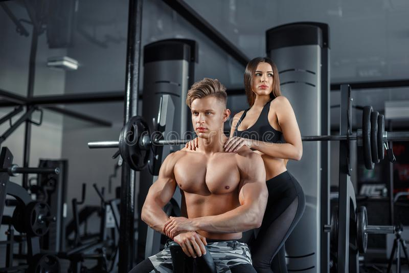Pares deportivos jovenes hermosos que muestran el músculo y el entrenamiento en gimnasio durante photoshooting fotos de archivo