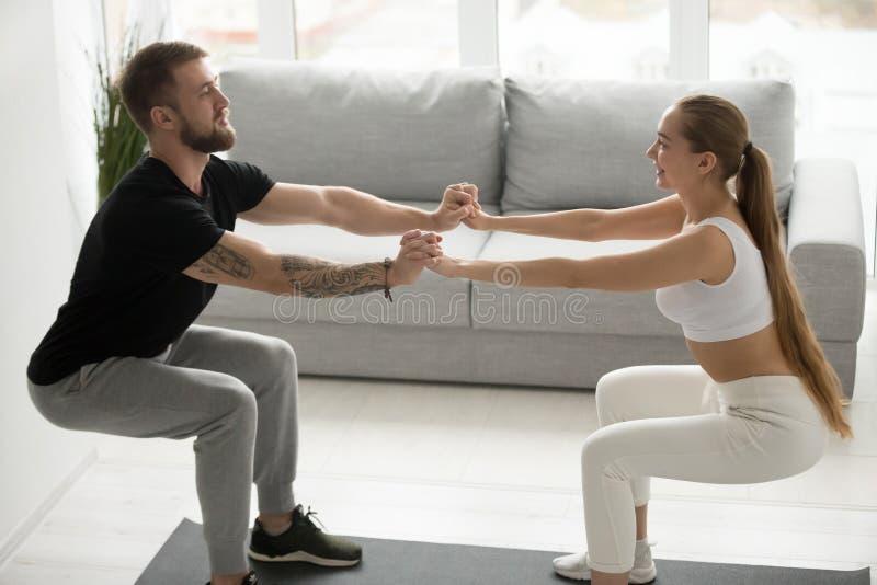 Pares deportivos jovenes que hacen las posiciones en cuclillas que llevan a cabo las manos juntas en casa foto de archivo libre de regalías