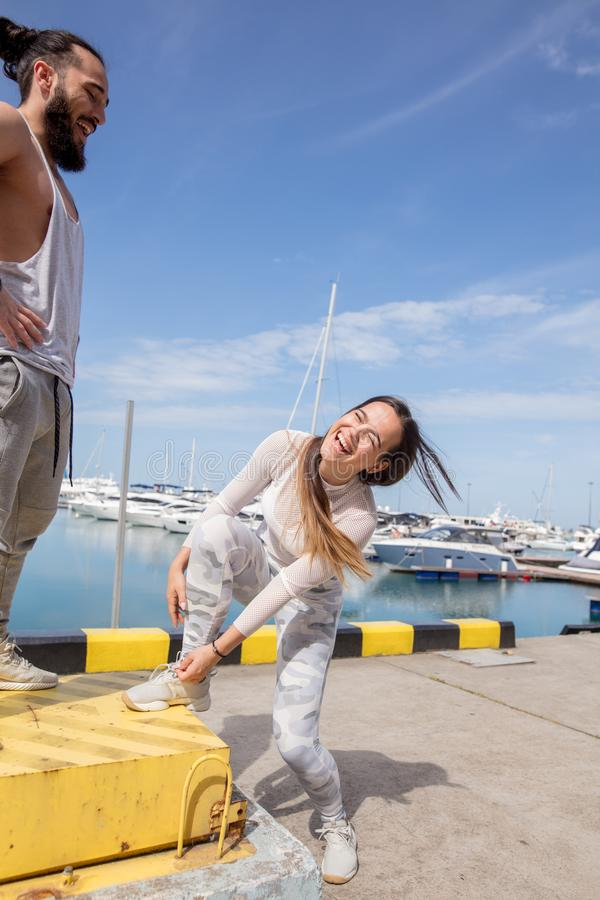 Pares deportivos jovenes que tienen una rotura entre el entrenamiento, preparándose para correr en el embarcadero imagen de archivo
