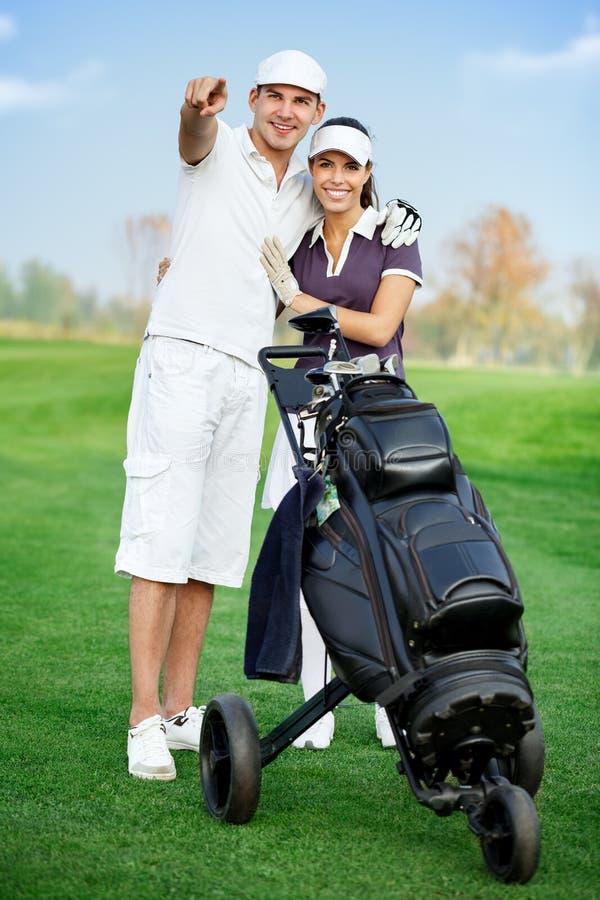 Pares desportivos novos que jogam o golfe foto de stock