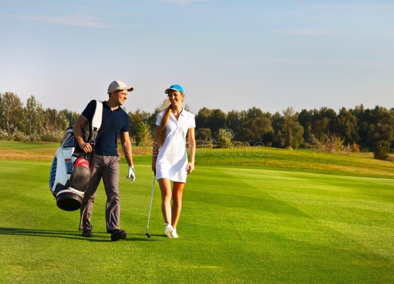 Pares desportivos novos que jogam o golfe imagem de stock royalty free