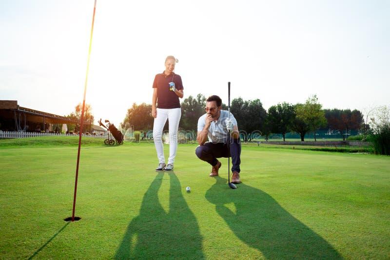 Pares desportivos novos que jogam o golfe em um campo de golfe fotografia de stock